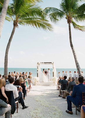 Bride and groom at altar in between two palm trees with flower petals on sand and urns at altar