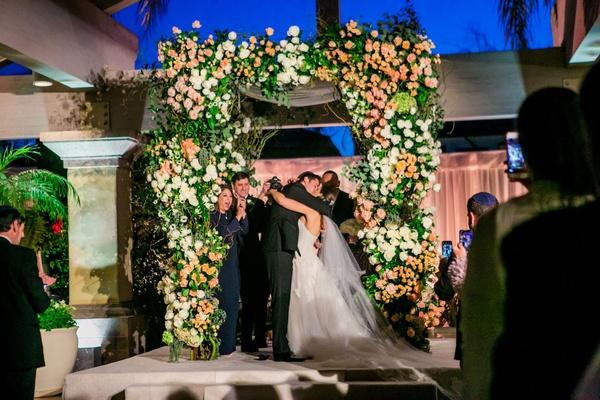 wedding ceremony arch chuppah white rose anemone peach pink blush orange flowers country club jewish