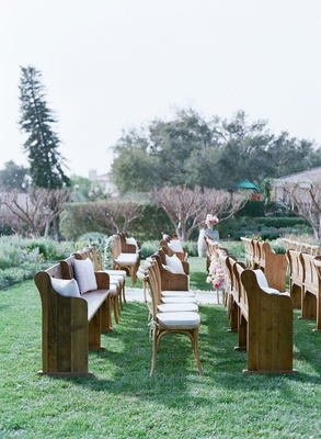 Outdoor garden wedding ceremony seating wood pews, pillows, and wood chairs