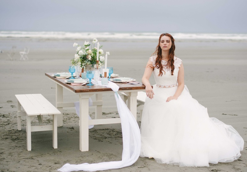 a simple blue and white tablescape on a white and brown wooden table with a bride on a beach