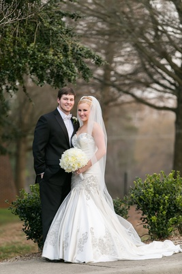 Blonde bride in gown with drop waist and man in tuxedo