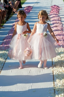 Two flower girls walk down petal-lined aisle