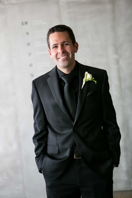 a groom in an all black tuxedo ensemble with simple white and green boutonniere