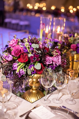 wedding reception purple lighting mirror with gold footed vase pink purple rose flowers greenery
