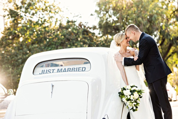 wedding photo of bride and groom in front of classic car with just married banner in back window