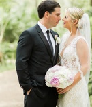 bride in alon livne lace dress looks into eyes of groom in hugo boss suit