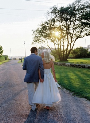 Bride and groom walk towards sunset on private estate
