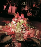 Red table linens with abundant flower centerpiece