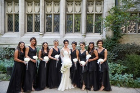 Bridesmaids in black dresses v neck holding white glamelia bouquets rose petals pearls feathers