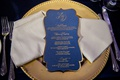 wedding reception gold charger plate napkin and navy blue menu card die cut gold border calligraphy