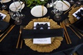 gold charger plate, black linen, wedding reception menu decorated with bow tie