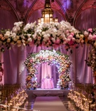 Gold and white checker floor candlelight lush pink orange white flower arch with chandelier