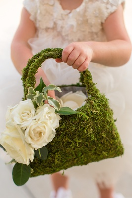 Green moss on flower girl purse with white roses