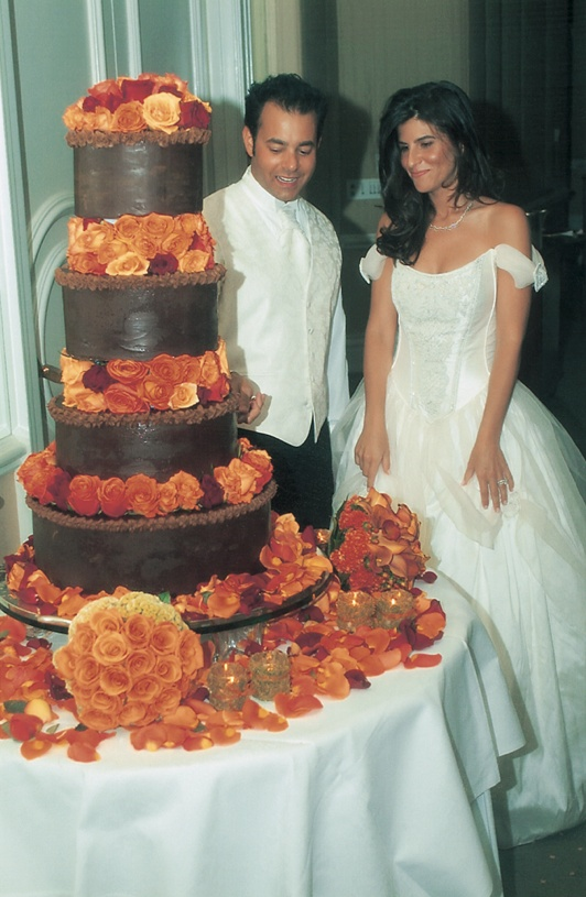 four tiered cake with brown frosting and orange roses