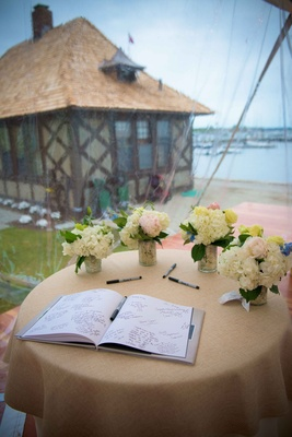 a couples guestbook sitting in the window of couples reception space overlooking a harbor