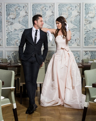 bride in le spose di gio blush gown and white gloves, leaning on shoulder of groom