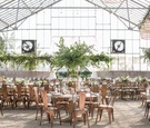 wedding reception greenhouse venue tall greenery trees industrial copper chairs high low centerpiece