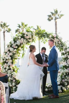 wedding ceremony arch flowers by cina bride and groom with officiant ocean view palm trees