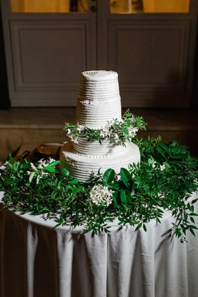 four tier white wedding cake on bed of greenery