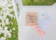 wedding ceremony grass lawn white flower petal white chair light pink fan program kraft paper toss