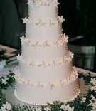 Five layer cake with flowers and frosting dots