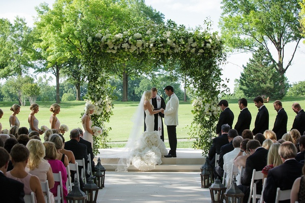 Bride in a fit-and-flare Vera Wang dress, ruffled skirt, veil & groom in white tux jacket at outdoor