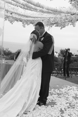 black and white couple kiss under flowers