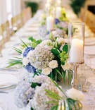 Head table with candles and low small centerpieces white rose blue hydrangea greenery
