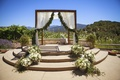 Rustic wedding chuppah with garland on fabric at ranch