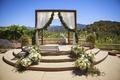 Rustic wedding chuppah with garland on fabric at ranch