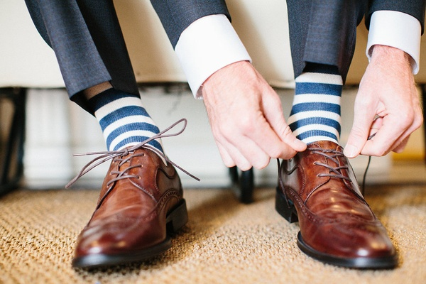 Groom wearing blue and white stripe socks with brown lace up wingtip dress shoes