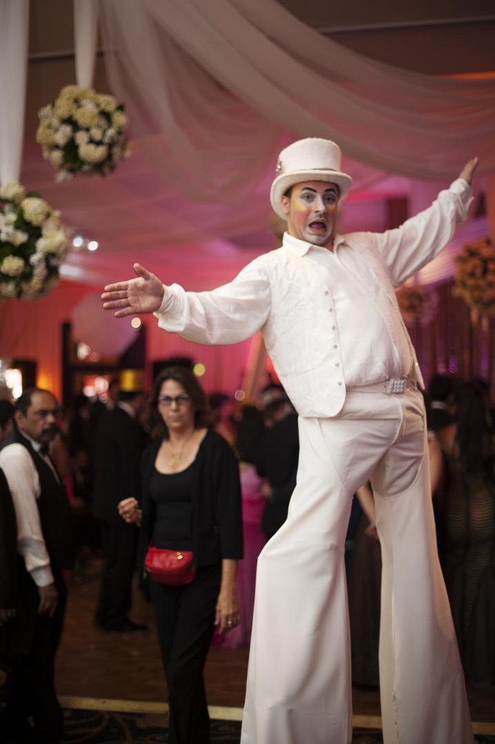Man in white top hat on stilts at wedding reception
