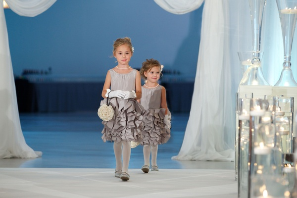 Two flower girls in ruffle skirt dresses in grey and gloves