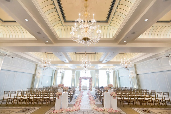 wedding ceremony ballroom casa del mar santa monica gold chairs white aisle runner pink flower petal
