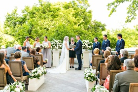 Wedding guests in wood chairs flower boxes stone aisle bride and groom woman officiant bridesmaids