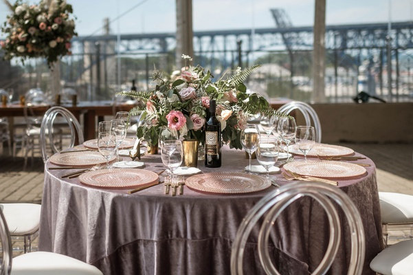 wedding reception greenery pink purple flowers velvet round table clear acrylic chairs lucite