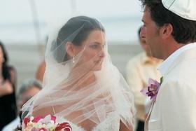 Beach wedding veil over bride's face
