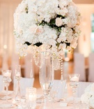 Wedding reception candles floating tall glass vases with white orchid hydrangea rose greenery flower