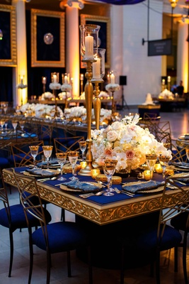 blue and gold tablescapes with tall gold candles and low white floral arrangements