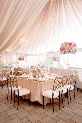 wedding reception tent blush pink gold chairs white pink flowers square table settee tufted sofas