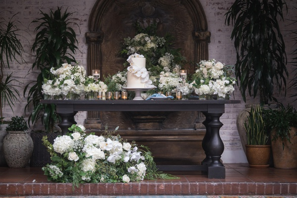 large table with small wedding cake, dessert table, white flowers and greenery