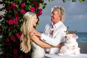 bride and groom in white suit jacket under ceremony arch cutting into white cake with pink flowers