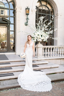 bride in pnina tornai wedding dress with lace cutouts and inserts