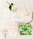 Tropical wedding invitation suite with green fronds and flamingos on the cover and map of Florida