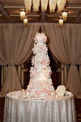 White wedding cake covered with white and pink sugar flowers
