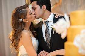 Bride with curled hair and sparkling brooch kisses groom