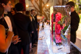 Wedding reception unique decor pink peony rose flower frozen in large ice cube at ice sculpture bar
