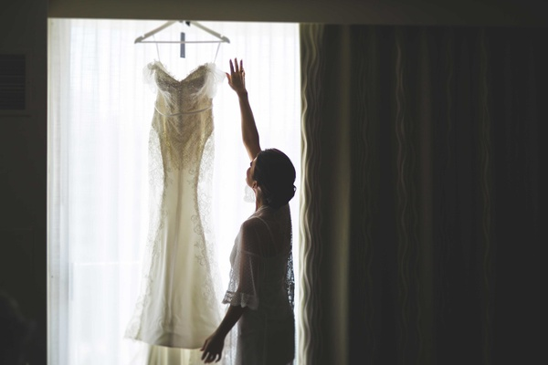 Bride in robe admires wedding dress hanging in window before wedding ceremony George Elsissa