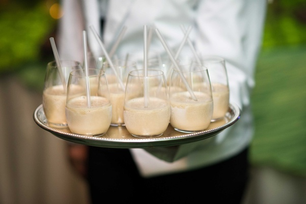 Server at wedding holding silver tray of Kahlua milkshake with clear straw desserts