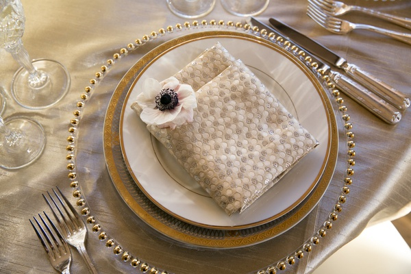 textured, patterned napkin at wedding reception with anemone blossom in the corner